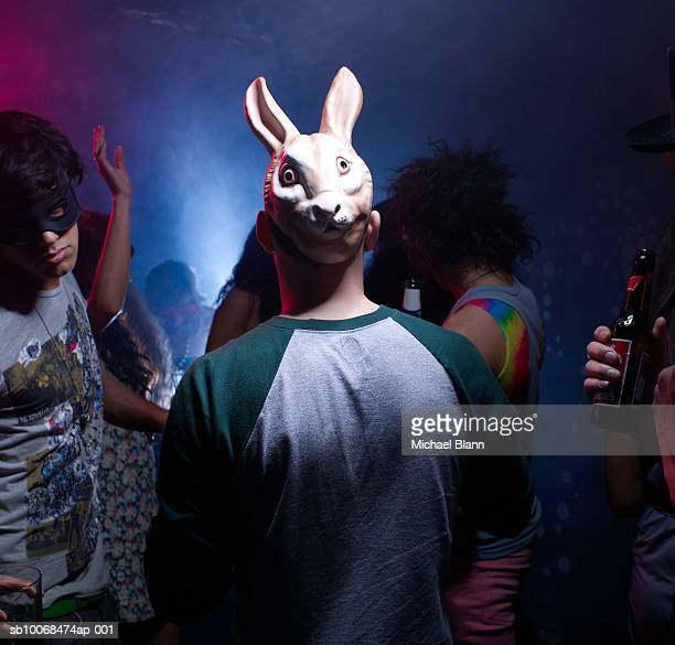 Man in bunny mask dancing in night club