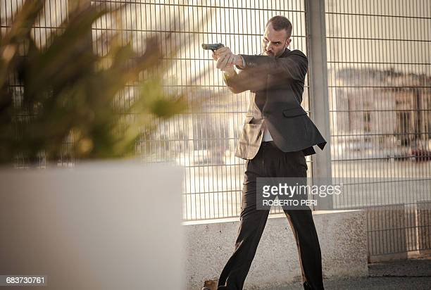 Man in business attire walking in harbour poised with handgun, Cagliari, Sardinia, Italy