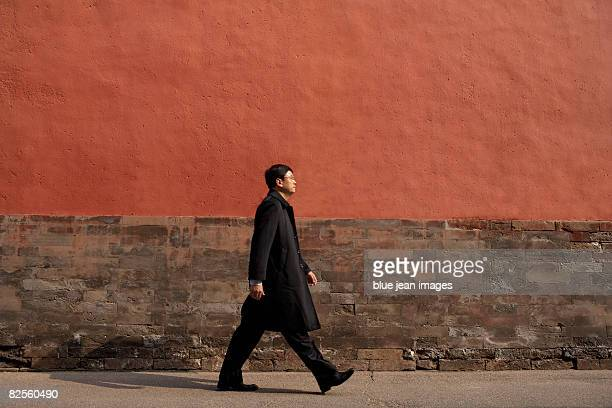 A man in business attire walks in front of a red wall.