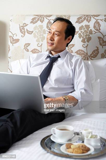 Man in business attire with laptop and tray of cookes and coffee