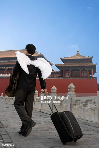 A man in business attire with wings, pulls a piece of luggage, Chinese architectural elements behind.