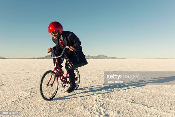 Man in Business Suit and Racing Helmet Races his Bicycle