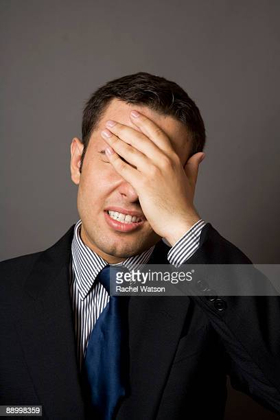 Man in business suit covering face with hand