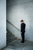 A man in business suit standing at the foot of a staircase on August 07 2014 in Berlin Germany