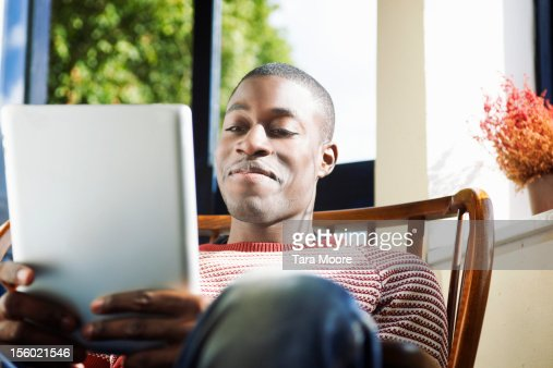 man in cafe smiling looking at digital tablet : Stock Photo
