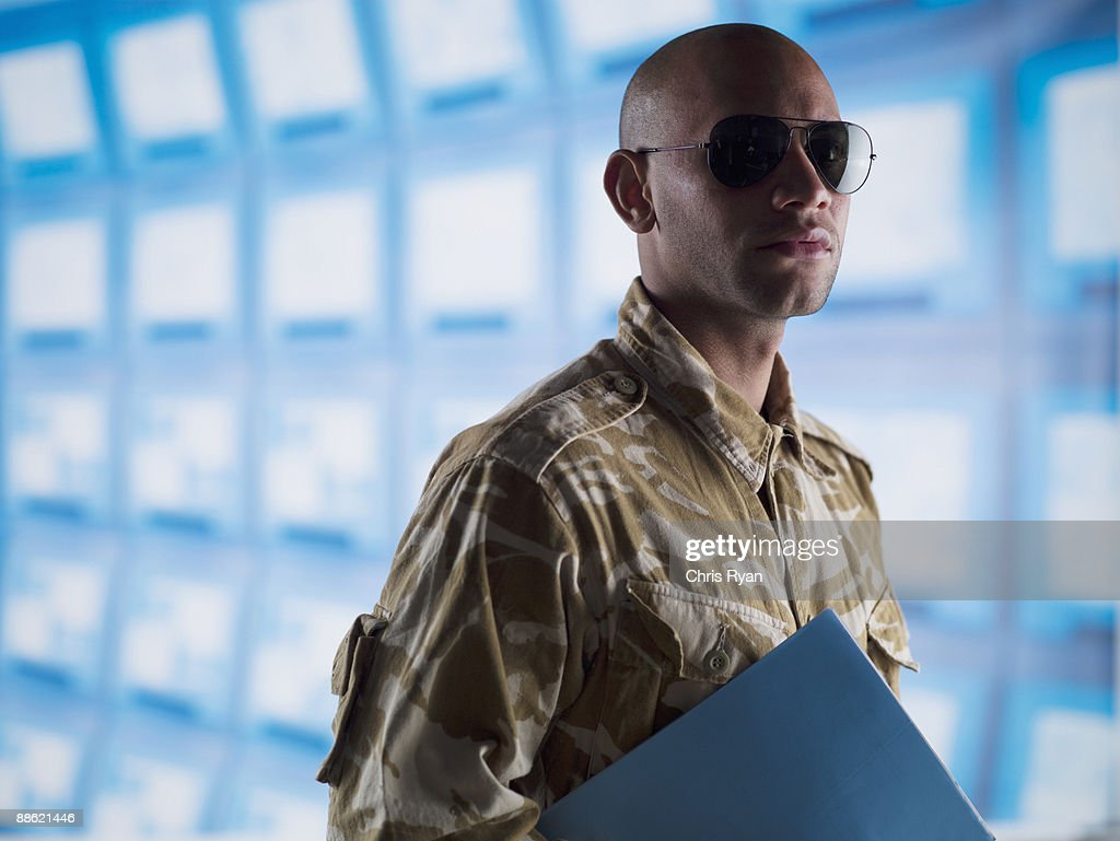 Man in camouflage holding folder near bank of computers : Stock Photo