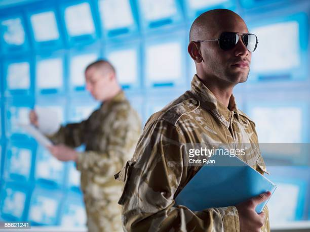 Man in camouflage holding folder