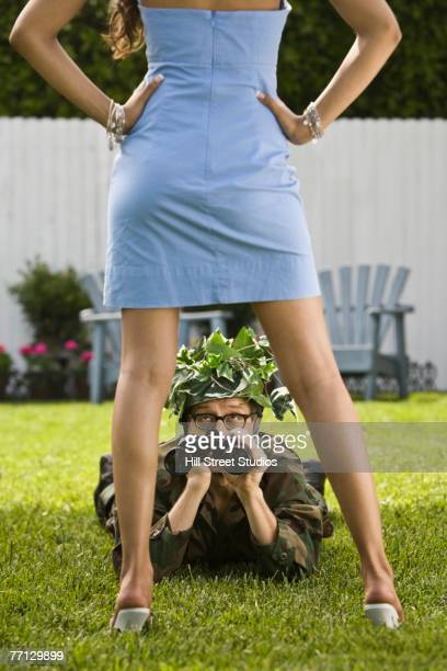 Man in camouflage looking up at woman