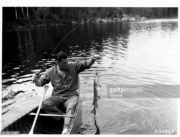 Man in canoe holding up a Northern Pike