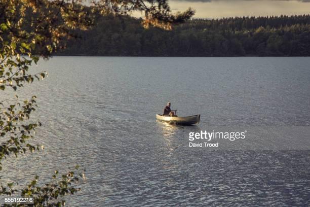 Man in canoe on a lake in Sweden