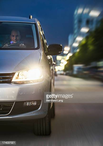 Man in car driving down urban road