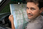 Man in car holding road map, smiling, portrait, close-up