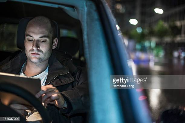 Man in car looking on tablet computer