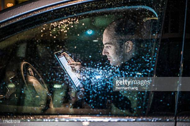 Man in car looking on tablet computer, side view