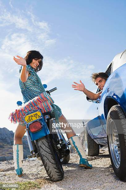Man in car woman on motorbike.