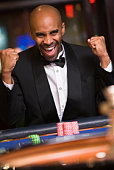 Man in casino winning roulette and smiling (selective focus)