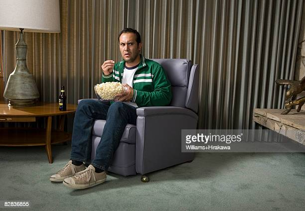 Man in chair eating popcorn