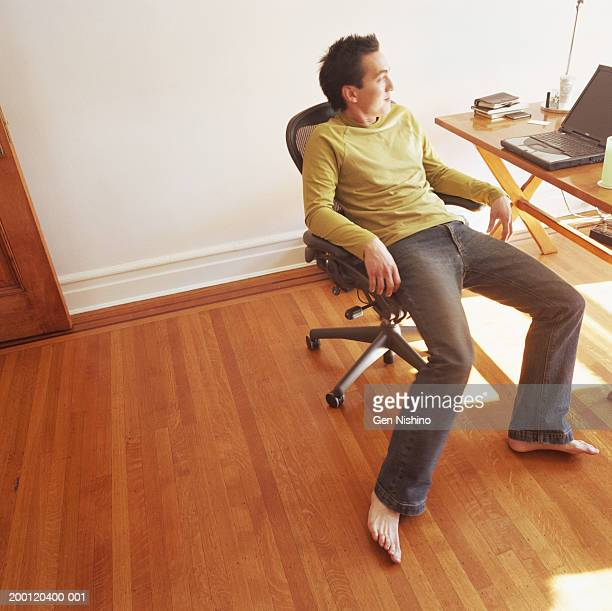Man in chair near table with laptop