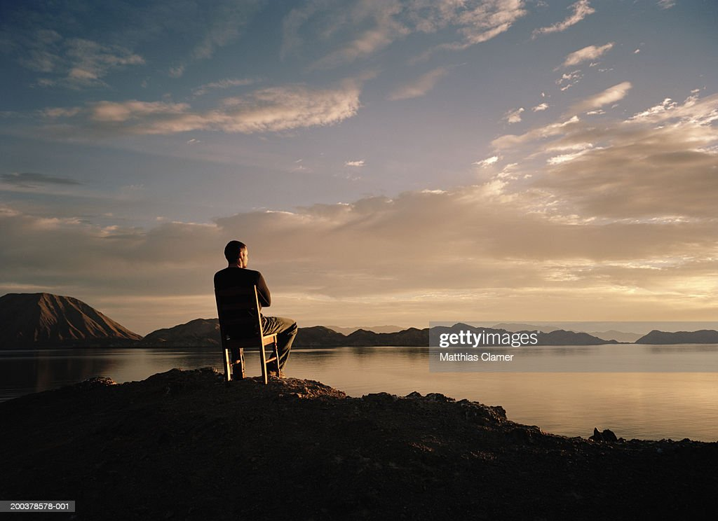 Man in chair watching sunrise over bay, rear view : Stock Photo