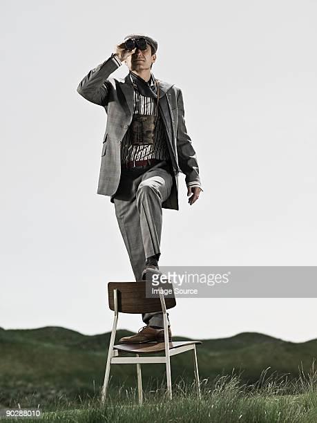 Mann im Stuhl mit Fernglas