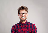 Hipster man in red checked shirt and eyeglasses. Studio shot on gray background