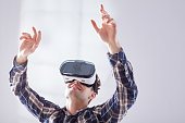 Man in checkered shirt pulls his hands up in the virtual game in white room
