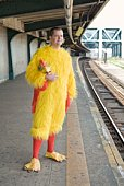 Man in chicken costume waiting for train