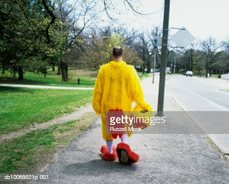 Man in chicken suit walking in park, rear view : Stock Photo
