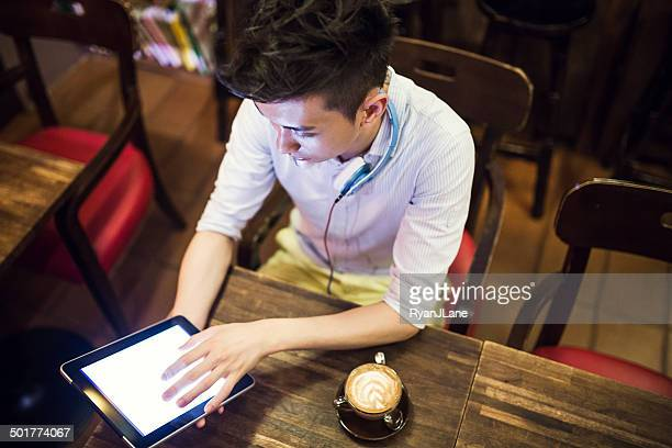 Man in Chinese Cafe on Digital Tablet