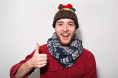 Man in Christmas pudding hat with thumbs up