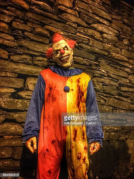 Man In Clown Costume Against Wall During Halloween
