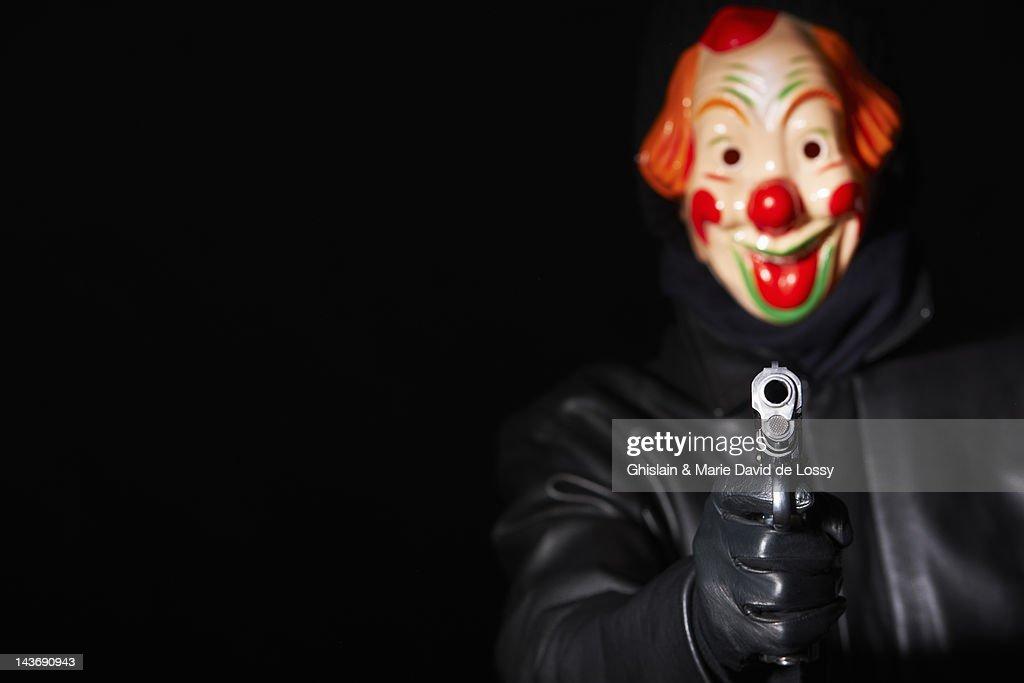 Man in clown mask pointing gun : Stock Photo