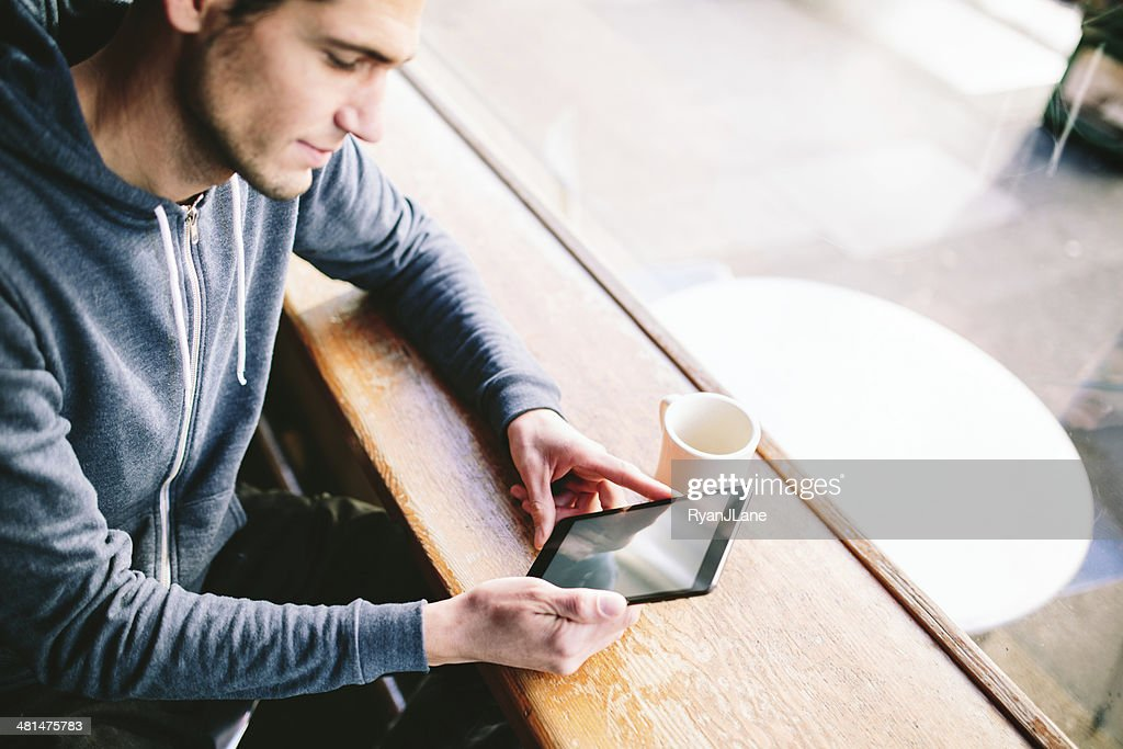Man in Coffee Shop on Tablet Computer : Stock Photo