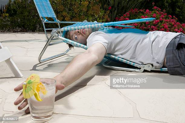 Man in collapsed deck chair, reaching for drink