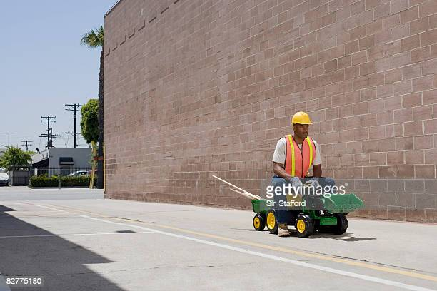 man in construction outfit on toy tractor