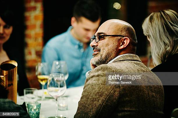 Man in conversation with friends during dinner