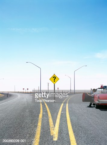 Man in convertable car at split in road, question mark traffic sign : Stock Photo
