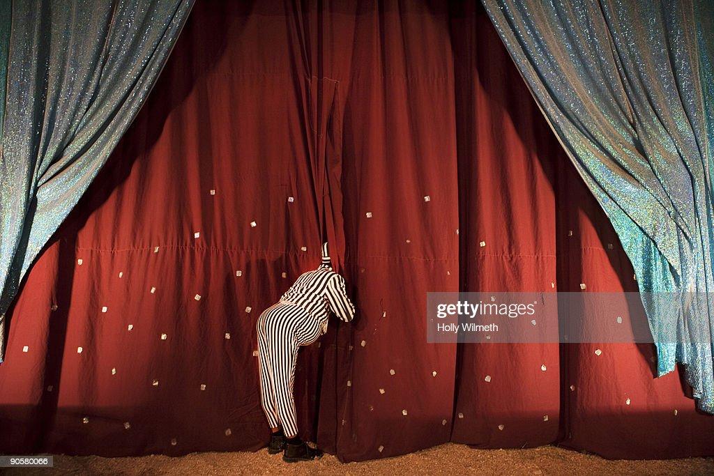 Man in costume peeking through stage curtain : Stock Photo