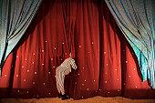 Man in costume peeking through stage curtain