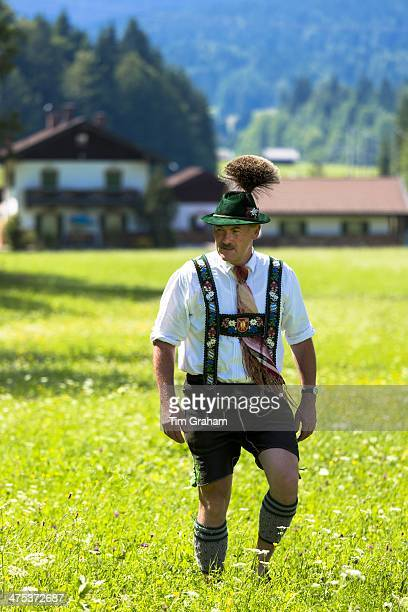 Man in costume strolls through flower meadow during traditional beer festival in the village of Klais in Bavaria Germany