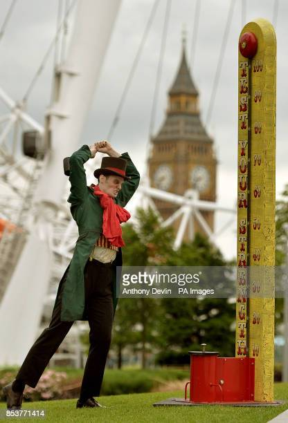 A man in costume tests his strength on the High Striker during a photo call for the London Dungeon's Carnivale side show featuring a giant 'Jeremy...