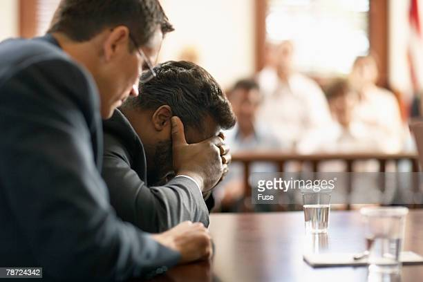 Man in Courtroom with Head in Hands