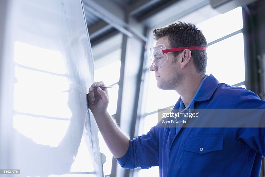 Man in coveralls writing on whiteboard : Stock Photo