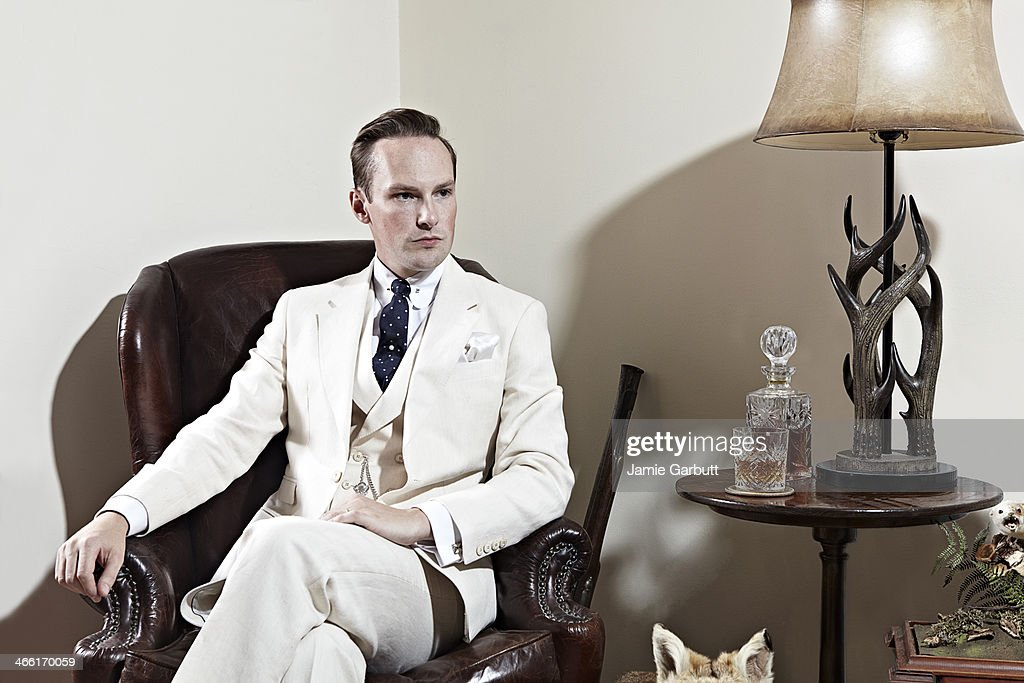 Man in cream suit sitting in chair with whisky. : Stock Photo