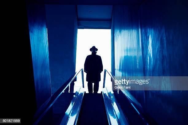 Man in dark hat and coat taking elevator