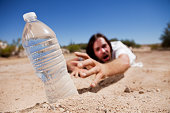 Dehydrated man crawling through the desert reaching for bottle of water.
