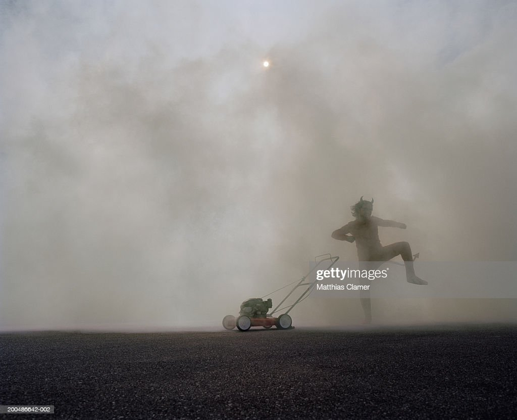 Man in devil's costume dancing next to lawn mower in smoke : Stock Photo