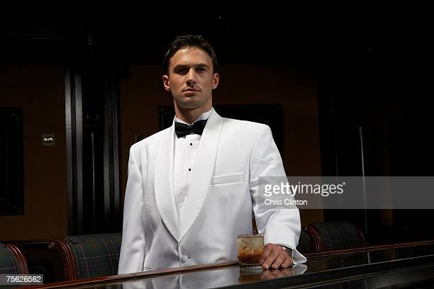 Man in dinner jacket standing at bar with drink, portrait