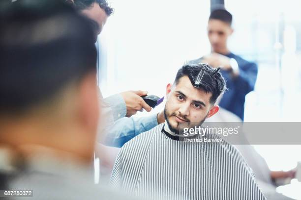 Man in discussion with friend while having hair cut in barber shop