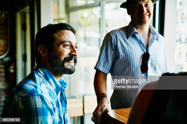 Man in discussion with friends in restaurant